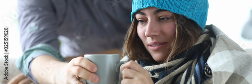 Portrait of joyful woman sitting indoors and holding cup of hot beverage that help cure annoying illness and wearing warm clothes indoors Canvas Print
