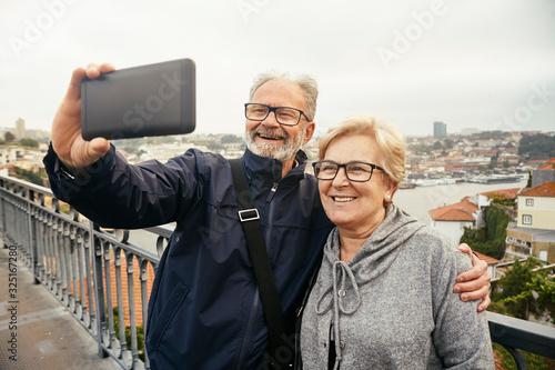 pareja de jubilados sacándose un selfie en un puente en Portugal Canvas Print