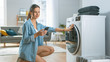 canvas print picture - Beautiful Young Woman Sits on Her Knees Next to the Washing Machine. She Loaded the Washer with Dirty Laundry While Using Her Smartphone. Shot in Living Room with Modern Interior.