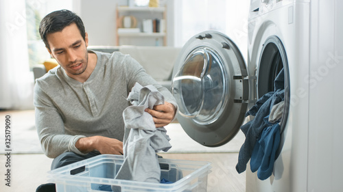 Valokuva Handsome Smiling Young Man in Grey Jeans and Jumper Sits in Front of a Washing Machine at Home