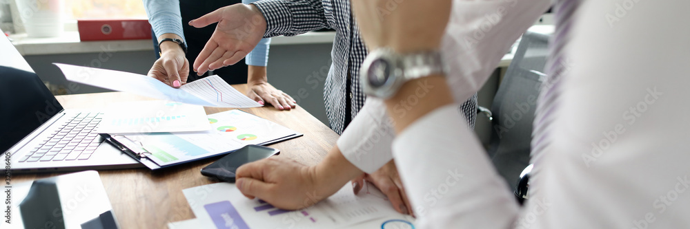 Fototapeta Close-up of people hands working with important documents. Colleagues discussing statistics data of new start-up. Office work environment. Teamwork concept