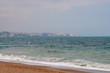 Un mar revuelto en azul verdoso con el fondo de una ciudad costera