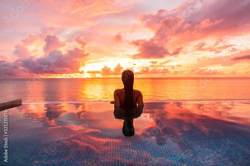 Fototapeta Paradise luxury resort honeymoon getaway destination at idyllic Caribbean tropical landscape hotel, woman silhouette swimming in infinity pool watching sunset serene. Winter getaway at dusk. obraz