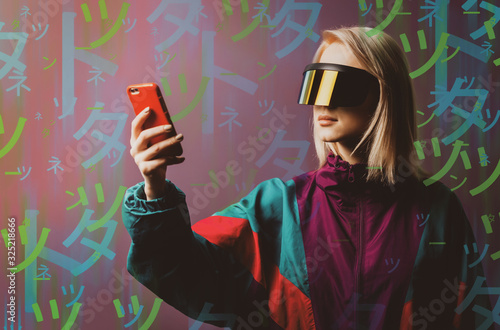 Photo Blonde in VR glasses, mobile phone and 90s sport suit with Japanese hieroglyphs