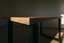 Detailed Texture Of Modern Wooden Table And Angular Iron Structures In Form Of Legs On Sides.Table Is In Empty Room With White Wall And Wooden Floor.Sunlight Falls On Table And Creates Contrast Scene.