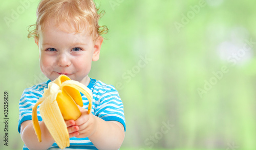 happy kid eating banana fruit Slika na platnu