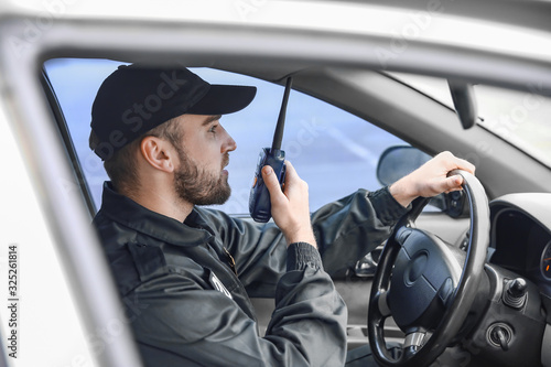 Male police officer driving car Fototapete
