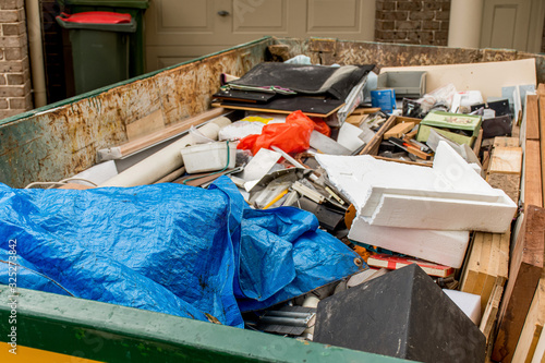 Skip bin full of household waste rubbish on the frond yard Canvas Print