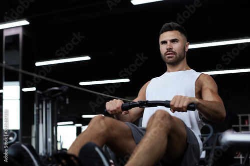 Photo Fit and muscular man using rowing machine at gym.