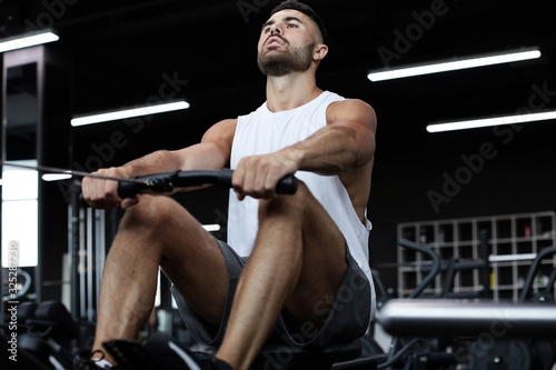 Fit and muscular man using rowing machine at gym. Wallpaper Mural