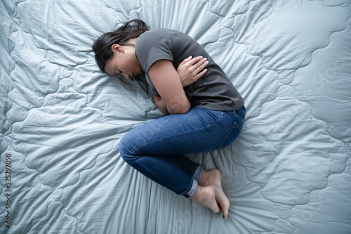 Photo Unhealthy young woman lying in bed feeling depressed