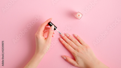 Woman applying polish on nails at home. Female hands with elegant manicure and nail polish bottle on pink background  top view. Beauty treatment and hand care concept