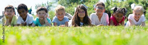 Obraz Happy children lie on the green grass on a sunny day - fototapety do salonu