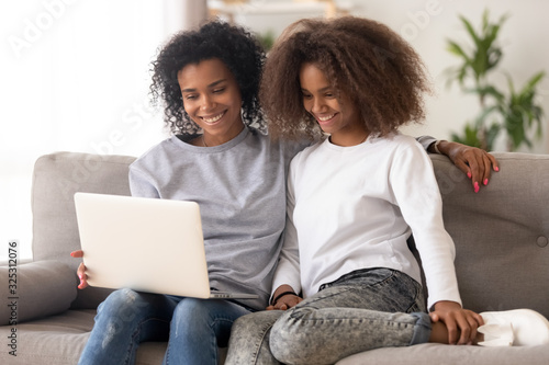 Happy african family mother and daughter use laptop on couch Wallpaper Mural