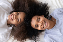 Happy African Mother And Daughter Lying On Bed, Top View