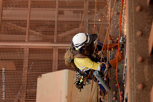 Photo Tope view of rope access technician welder services wearing white helmet head fa