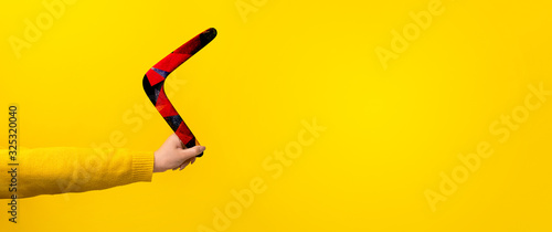 boomerang in female hand over yellow background, panoramic mock-up with space fo фототапет