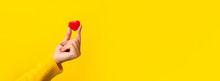 Hand Holding Small Red Heart Over Yellow Background, Panoramic Mock-up