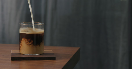 cream pour into coffee in glass on walnut table