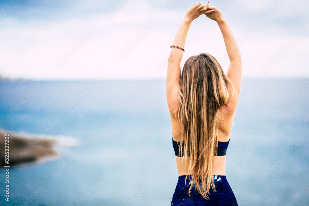 Fototapeta Healthy lifestyle people concept with beautiful long blonde hair girl viewed from back do some stretching in front of the ocean view outdoor - fit woman and attractive female