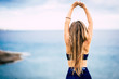 Leinwanddruck Bild - Healthy lifestyle people concept with beautiful long blonde hair girl viewed from back do some stretching in front of the ocean view outdoor - fit woman and attractive female