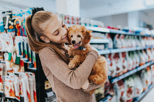 Obraz Cute girl with her poodle puppy in pet shop. - fototapety do salonu