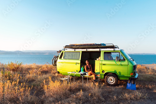 Tela Young attractive female sitting in old timer camper van on a hill above the beach looking at the golden light of sunset