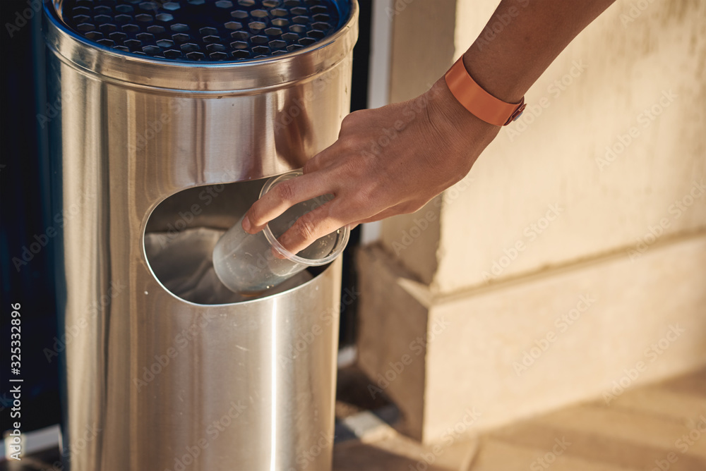 Fototapeta Woman hand throwing plactic cup for water in a trash bin