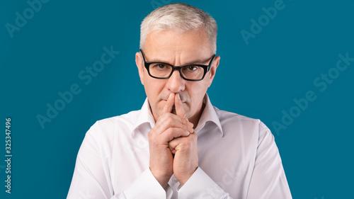 Fotografie, Obraz Senior pensive man portrait on dark blue background