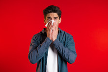 Young Man Sneezes Into Tissue....