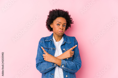 Photo Young african american woman against a pink backgroound isolated points sideways, is trying to choose between two options