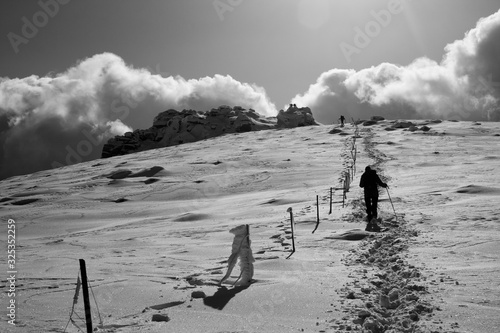 Photo backlit hiker in the distance ascending next to a fence a snowy mountain in blac