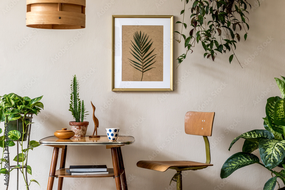 Fototapeta Retro interior design of living room with stylish vintage chair and table, plants, cacti, personal accessories and gold mock up poster frame on the beige wall. Elegant home decor. Template.