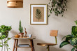Leinwanddruck Bild - Retro interior design of living room with stylish vintage chair and table, plants, cacti, personal accessories and gold mock up poster frame on the beige wall. Elegant home decor. Template.
