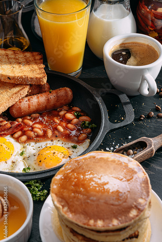 English breakfast on a dark table. fried eggs with bacon canned beans and sausage. near coffee, orange juice and pancakes with butter and honey © Mikhaylovskiy