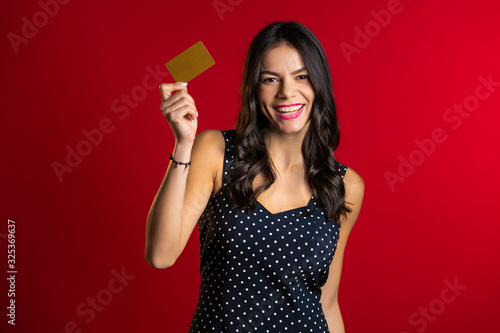 Fototapeta Successful pretty latin girl look to camera and showing unlimited gold credit card on red studio background.  obraz na płótnie