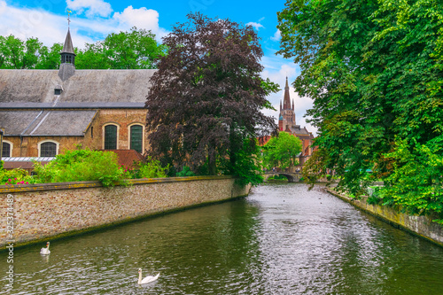 Photo Bruges, Belgium, a picturesque view from the canal of Beginage and Onze-Lieve-Vr