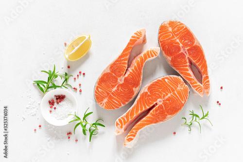 Fototapeta Salmon. Fresh raw salmon fish steaks with cooking ingredients, herbs and lemon on white background, top view obraz