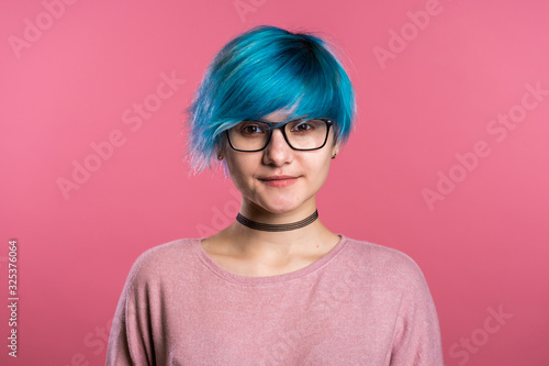 Portrait of young punk unusual woman with blue hair on pink background Canvas Print