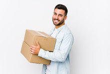 Young Caucasian Man Moving To A New Home Isolated Looks Aside Smiling, Cheerful And Pleasant.