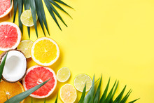 Summer Holidays, Resort Vacation, Exotic Fruits Background. Summertime Vibes. Composition With Citrus Slices On Yellow Surface, Copy Space