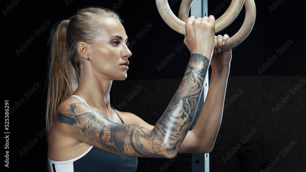 Fototapeta Female crossfit caucasian athlete in black sportswear exercising on gymnastic rings at gym Exercising woman holding gymnast rings Workout at gym.