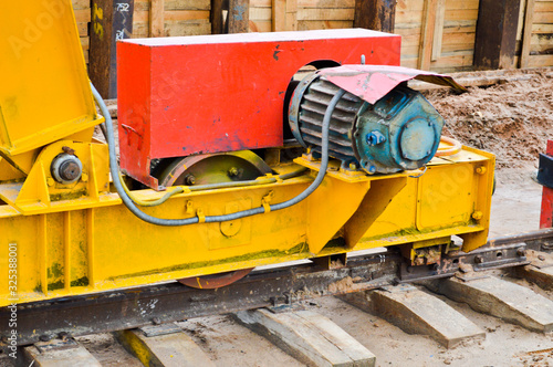 Large iron metal yellow supports on rails with wheels with an induction motor of Canvas Print