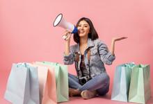Asian Pretty Young Woman Sitting On Pink  Pastel Background. She Smiling And  Happy Shopping Bags. She Nice-looking Lovely Attractive Shine She Holding Mobile.