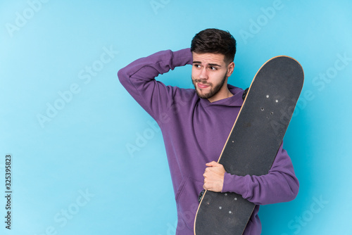 Valokuvatapetti Young caucasian skater man isolated touching back of head, thinking and making a choice