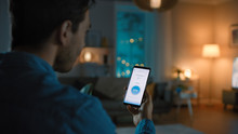 Young Handsome Man Gives A Voice Command To A Smart Home Application On His Smartphone To Switch On The Lights And Set A Comfortable Temperature. It's A Cozy Evening In Living Room.
