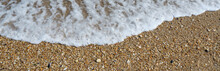 Small Smooth Pebbles And Worn Glass Line The Beach At Low Tide In The Coastal Community Of Sea Girt New Jersey On The Atlantic Coast As Small Foamy Waves Wash Over Them