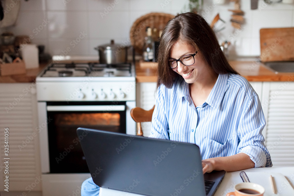 Fototapeta Young woman working from home office. Freelancer using laptop and the Internet for shopping online. Happy girl smiling. Workplace in cozy kitchen. Successful female business. Lifestyle moment.