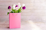 Spring flowers. Blooming tulips in pink shopping bag at wooden background. White, lilac and purple bouquet. Still life in morning sun light. Presents for holidays. Copy space.