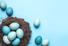Easter Eggs In Nest On Blue Background. Flat Lay, Top View.